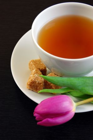 afternoon break: A cup of tea with cubes of brown sugar and a tulip on the plate Stock Photo