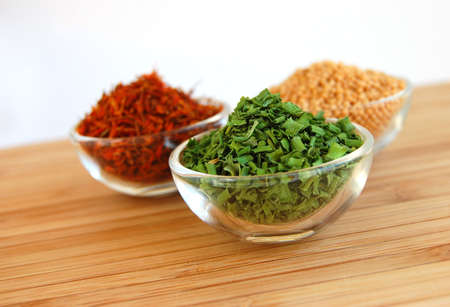 Three glass containers with saffron, mustard seed and chive on a wooden cutting desk Stock Photo