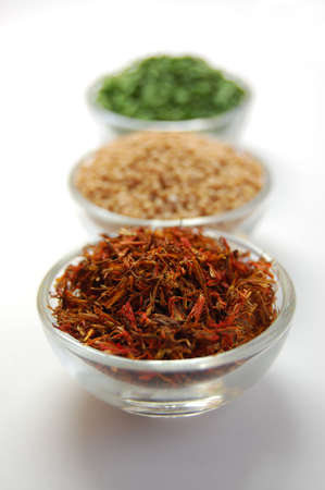 Three small glass containers filled with dry spices; saffron, chive and mustard seed photo