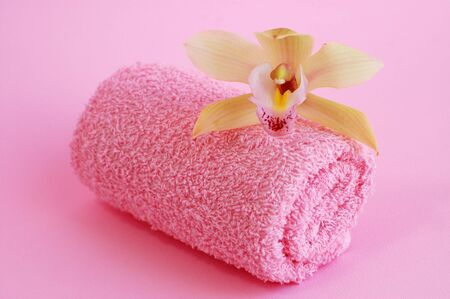 Delicate orchid on a pink towel with a pink background photo