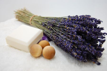 A bouquet of dry lavender, natural soap, and three aromatic wooden balls on a soft white towel with a white background