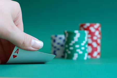 tokens: Womans hand lifting an ace with three piles of casino tokens on a green background