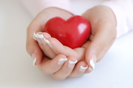 Young woman with beautiful long nails holding a wooden red heart