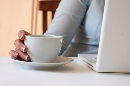 A woman with beautiful nails holds a cup of coffee as she uses a laptop photo