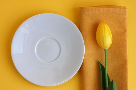 White plate and a yellow tulip on a napkin