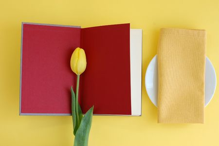 Yellow tulip on an open red book and an empty plate with a napkin