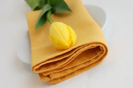 served: Yellow tulip and a napkin on a white plate Stock Photo