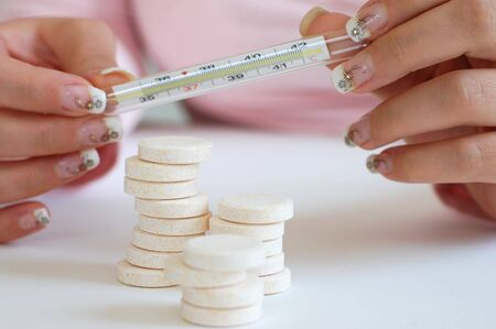 A woman with beautiful nails holding and reading a thermometer and a pile of vitamins photo