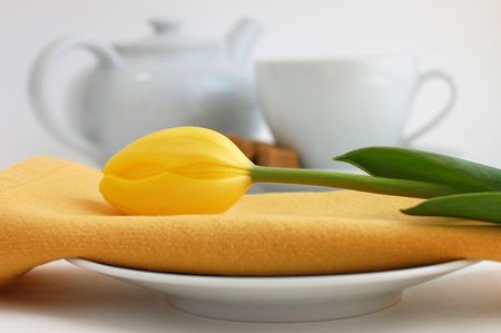 White plate and a yellow tulip on a napkin with a cup of tea and tea pot in the background photo