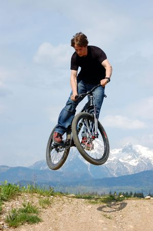 Teenager making tricks on a bicycle photo