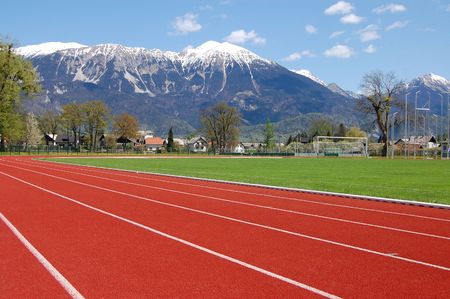 Racing track at the stadium under the snowcapped mountains in spring photo