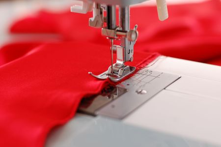 Sewing machine detail with the red thread and cloth photo