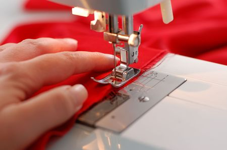 A hand of a dressmaker supporting a cloth while sewing on a sewing machine