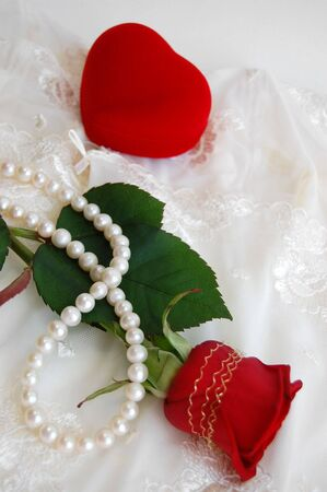 Red rose, pearl necklace and a heart-shaped ring box photo