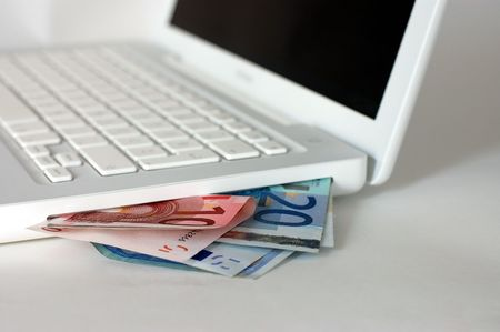 Euro bills and the computer (online shopping concept)