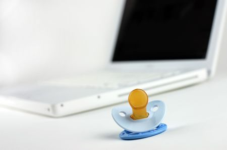 Blue pacifier with laptop in the  (working mother concept)