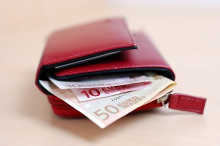 Open red leather wallet with euro banknotes