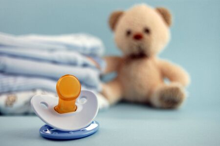 Blue pacifier and a pile  clothes and a teddy bear in the background photo