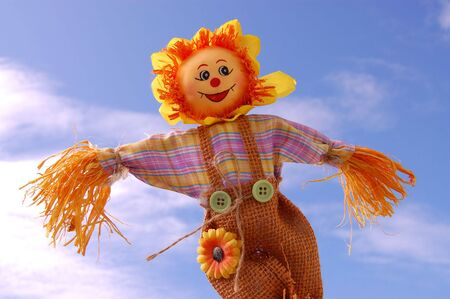 Smiling scarecrow against the blue sky