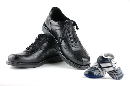 A pair of black mans shoes and a pair of blue baby shoes for the newborn. Father and son concept. Stock Photo