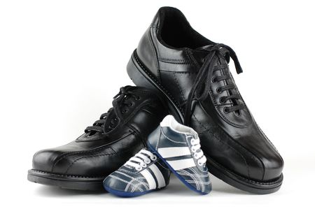big shoes: A pair of black mans shoes and a pair of blue baby shoes for the newborn. Father and son concept. Stock Photo
