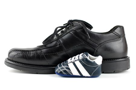 concep: A black mans shoe and a blue baby shoe for the newborn. Father and son concep