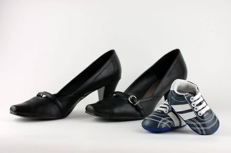 A pair of elegant womans shoes and a pair of blue baby shoes. Mother and son concept. photo