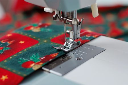 Sewing fabric with Christmas pattern with a sewing machine photo