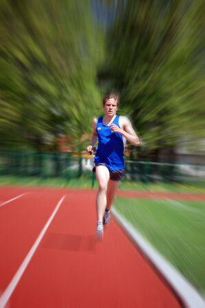 fast lane: Joven atleta corriendo en la pista de atletismo con la celebraci�n de un cron�metro de movimiento borroso