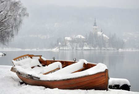 Wooden boat covered with snow with a church on an island in the misty background photo