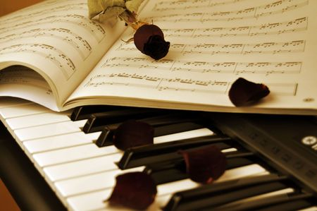 Dried red rose, music sheet and dry rose petals on a piano keyboard photo