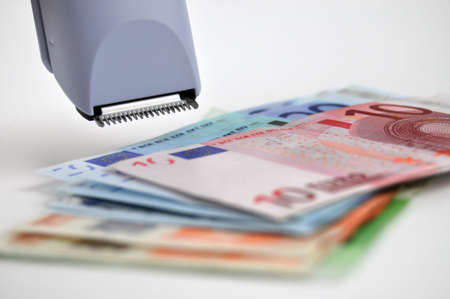 cutting costs: Euro banknotes and clipper (cutting costs concept)