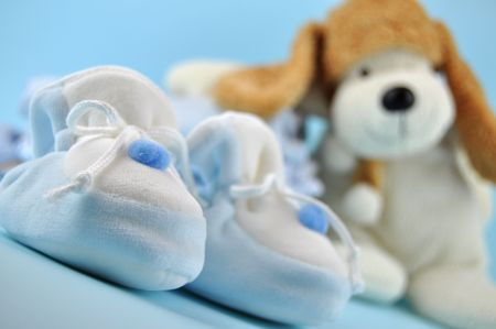 Blue baby sleepers and a toy dog