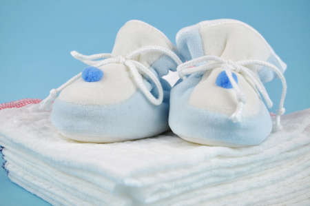 Blue baby sleepers on a pile of cotton diapers photo