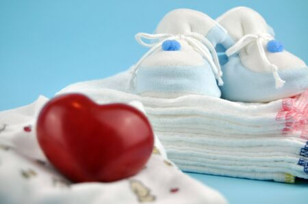 Red wooden heart with baby shoes on a pile of white cotton diapers in the background Stock Photo - 4280254