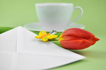 Red tulip and wooden butterfly on a white envelope with a cup of tea in the background photo