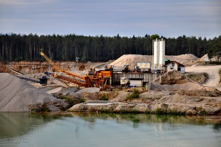 Stone quarry with silos, conveyor belts, and other mining equipment by the water