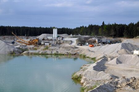 Stone quarry with silos, conveyor belts, and other mining equipment by the water photo