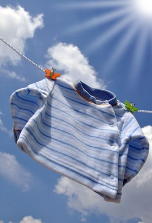 Sun shining on a small blue baby sweater hanging outside