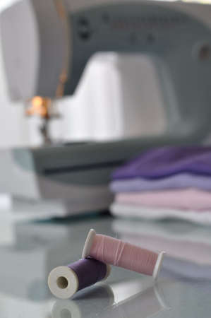 Two spools with pink and lilac thread with a sewing machine and clothes in the background photo