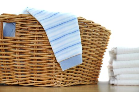 Laundry basket with blue clothes and a pile of diapers photo