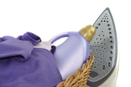 A detergent bottle and purple laundry in a wicker basket with iron