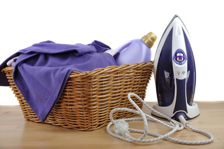 A detergent bottle and purple laundry in a wicker basket with iron on a wooden table