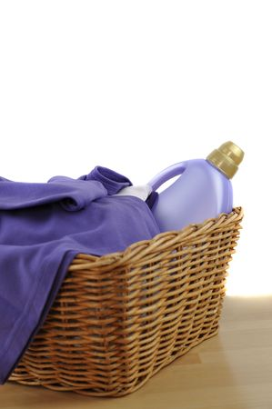 A detergent bottle and purple laundry in a wicker basket photo