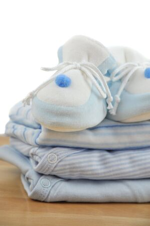 Blue baby slippers on a pile of baby clothes photo