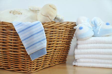 tela blanca: Canasta de lavander�a con la ropa azul y zapatillas en un mont�n de pa�ales