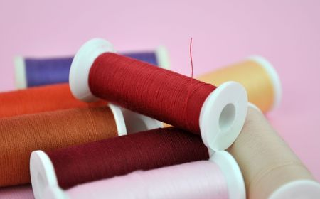 A pile of colorful spools on pink photo