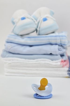 Pacifier with a pile of blue baby clothes, diapers, and booties in the background photo