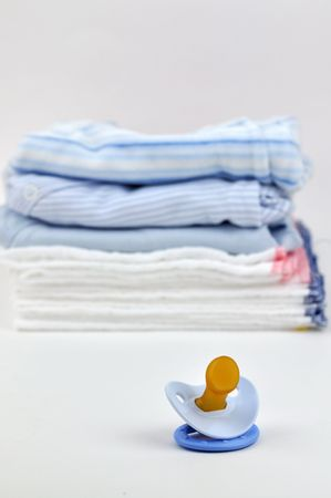 Pacifier with a pile of blue baby clothes and diapers in the background Stock Photo - 5055400