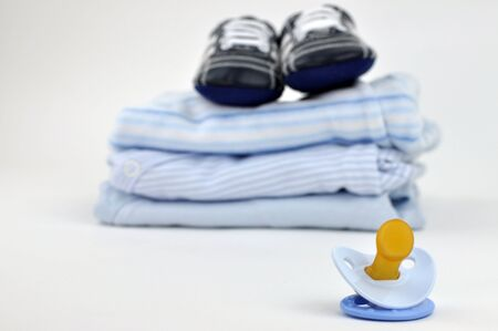Pacifier with a pile of blue baby clothes and booties in the background photo